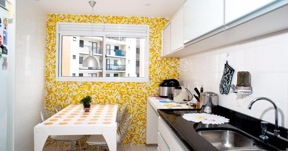 A parede revestida de pastilhas Vidrotil, assim como a mesa de refeições, recoberta por azulejos pintados à mão, deram o colorido a essa pequena cozinha projetada pelo escritório Oito Arquitetura
