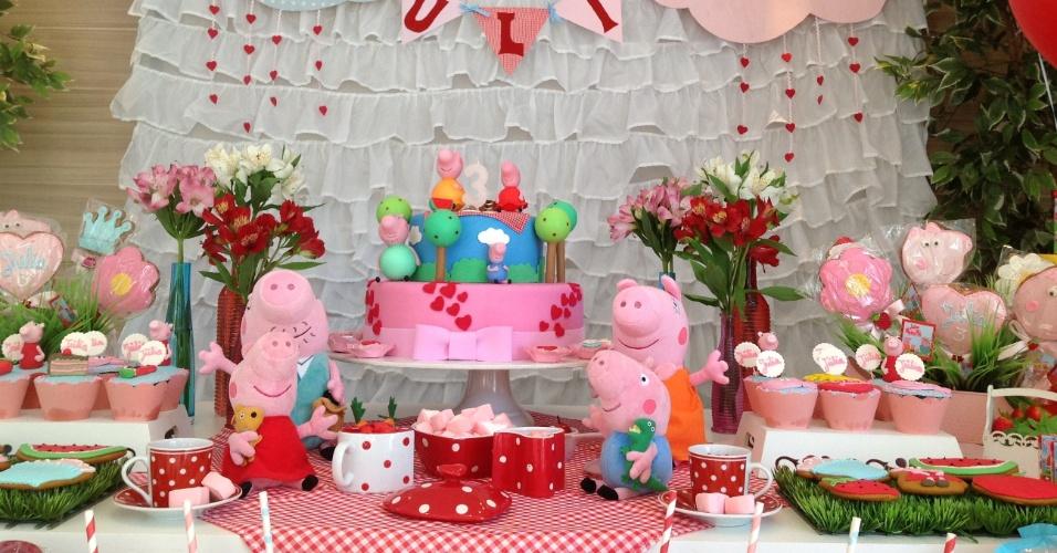 Nessa decoração com o tema Peppa Pig, montada pela empresa Ama Eventos, uma cortina de babados, com aplicações em feltro, serviu como painel da mesa principal, na qual ainda foram utilizados arranjos de astromélias e plantas artificiais