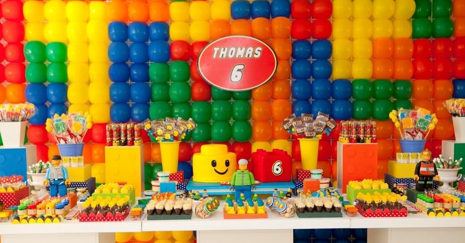 Os brinquedos da Lego são o tema dessa festa produzida pela empresa Komemore (www.komemore.blogspot.com). O painel ao fundo foi montado em uma estrutura de ferro, com bexigas coloridas imitando as pecinhas. O bolo, em estilo maquete, foi todo feito em pasta americana. Os bonecos foram confeccionados em biscuit