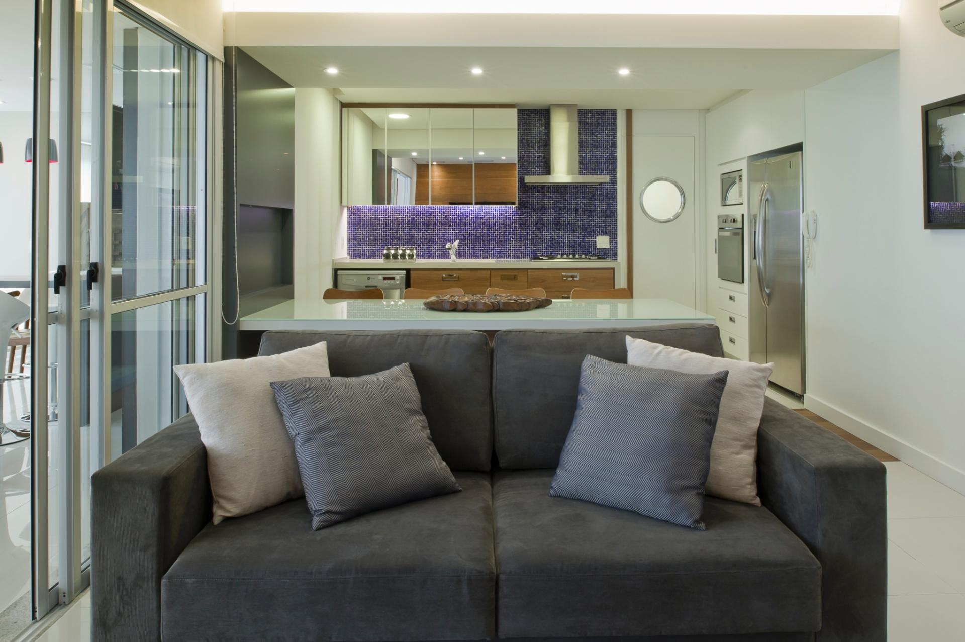 No projeto de reforma do apartamento, a parede que dividia a cozinha da sala foi derrubada para entrar uma grande mesa que no dia a dia serve como aparador, mas pode comportar até oito pessoas