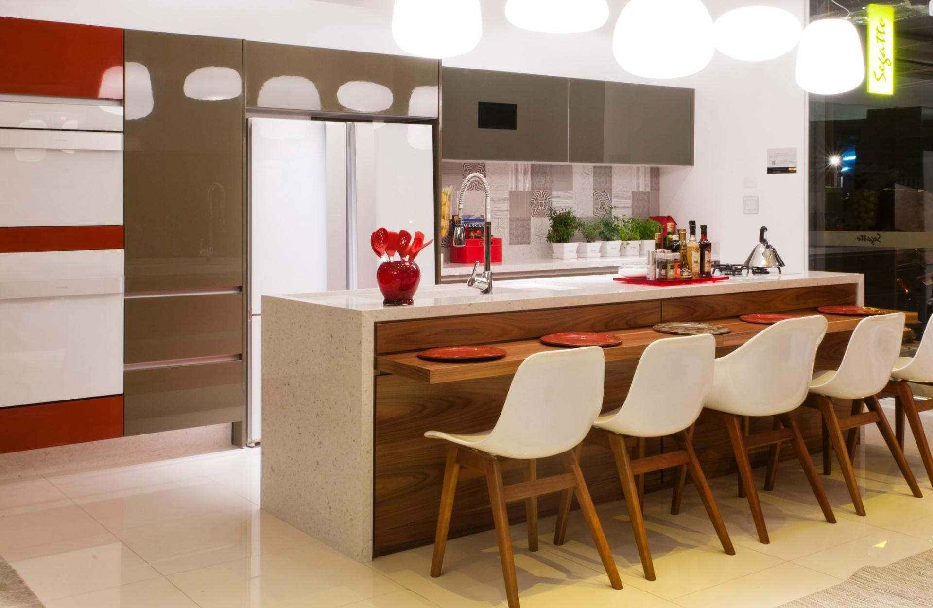 Integre sua cozinha à área de jantar e faça as refeições em família. O ambiente projetado pela arquiteta Irene Torre em parceria da marca Segatto prezou por uma mescla de cores e texturas, como madeira e vidro colorido