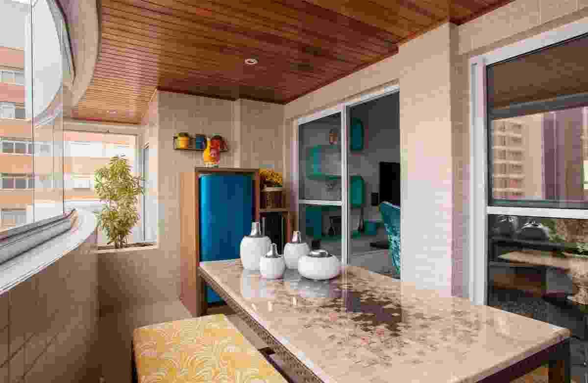 O espaço de 11m² transformou-se numa varanda gourmet com churrasqueira, bancos e uma grande mesa central, cujo tampo é feito com mosaico de pedras de mármore recortadas e resina - J. Vilhora/Divulgação