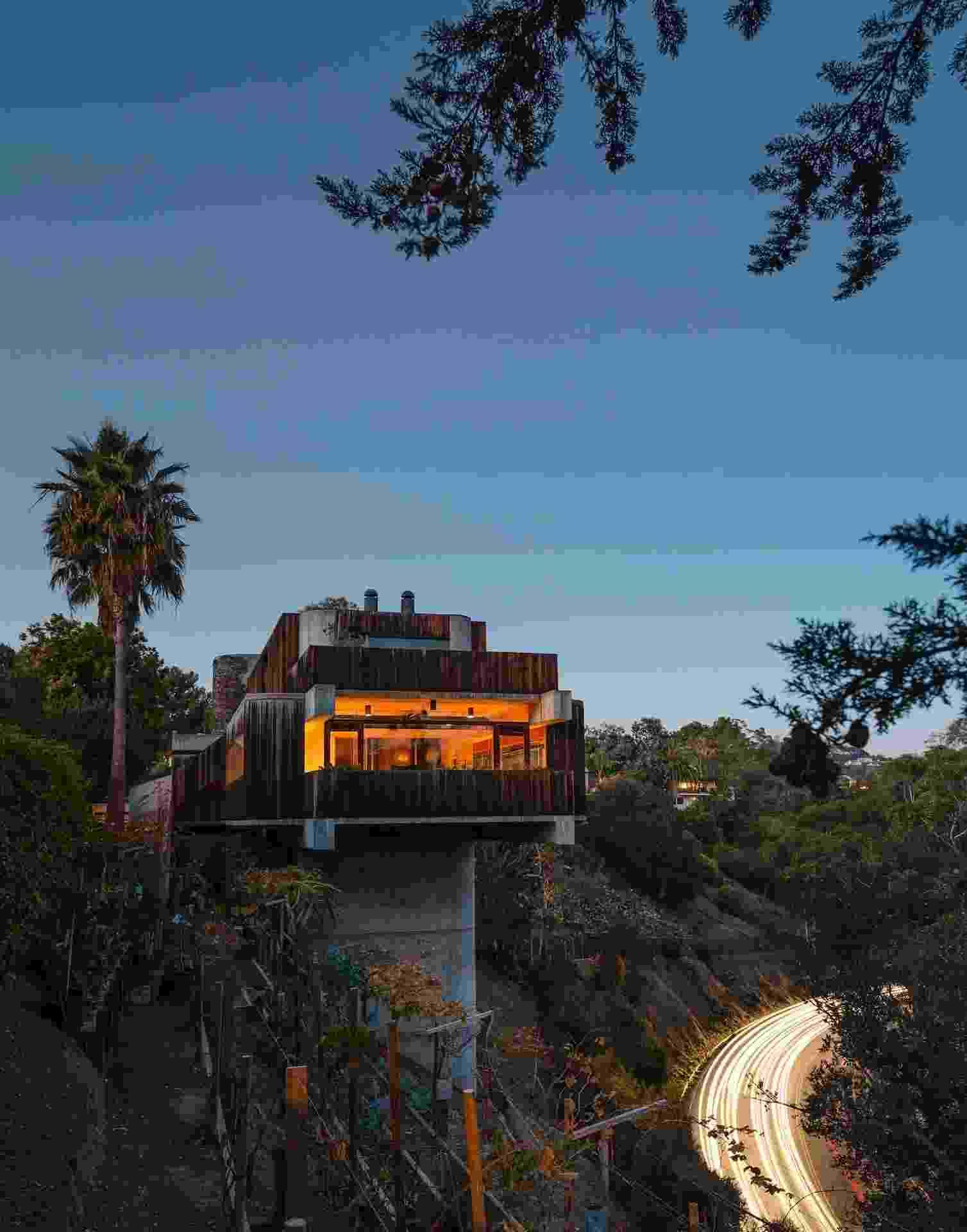 Ao anoitecer, as luzes da casa são acesas e sua arquitetura brutalista se destaca sobre terreno íngreme, ao lado da estrada Sunset Boulevard, em Los Angeles. Conforme o projetista e morador da residência, Robert Bridges, o projeto atrai turismos e estudantes de arquitetura - Trevor Tondro/The New York Times