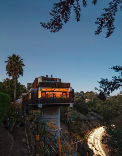 Ao anoitecer, as luzes da casa são acesas e sua arquitetura brutalista se destaca sobre terreno íngreme, ao lado da estrada Sunset Boulevard, em Los Angeles. Conforme o projetista e morador da residência, Robert Bridges, o projeto atrai turismos e estudantes de arquitetura