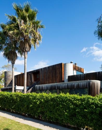 Enquanto a vista da casa para quem passa pela estrada Sunset Boulevard, em Los Angeles, evidencia a ousadia do projeto, sua entrada, no nível de uma rua residencial, é quase modesta