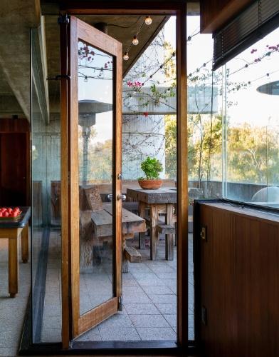 No interior da casa, a estrutura de concreto se mistura aos acabamentos e móveis feitos de madeira. Ao lado da cozinha, uma varanda se estende sobre a via movimentada da Sunset Boulevard, em Los Angeles