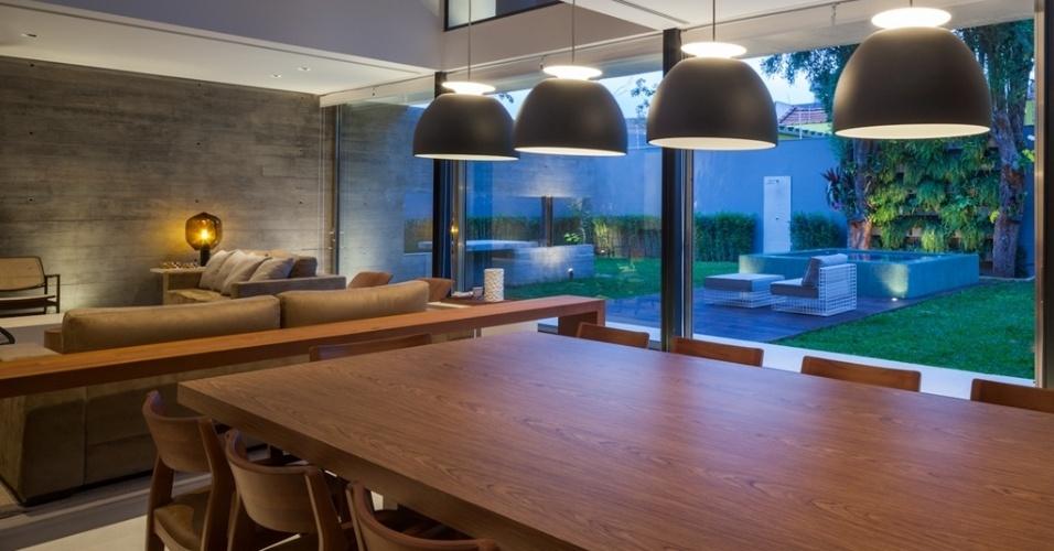 A mesa e o apoio para jantar são fabricados em madeira nogueira. O tom da marcenaria acompanha as variações do bege ao marrom das poltronas e sofás