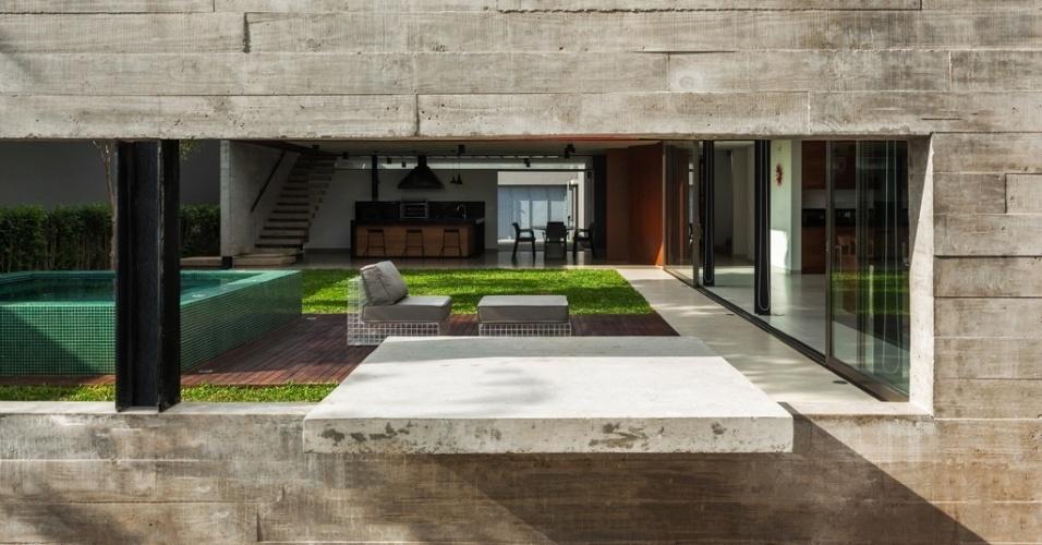 A parede estrutural em concreto que se estende nos fundos da residência e se projeta em direção ao jardim com ofurô contém um recorte para tampo de uma mesa a céu aberto, também em concreto. Com arquitetura de Flavio Castro, a Casa Planalto fica em São Paulo