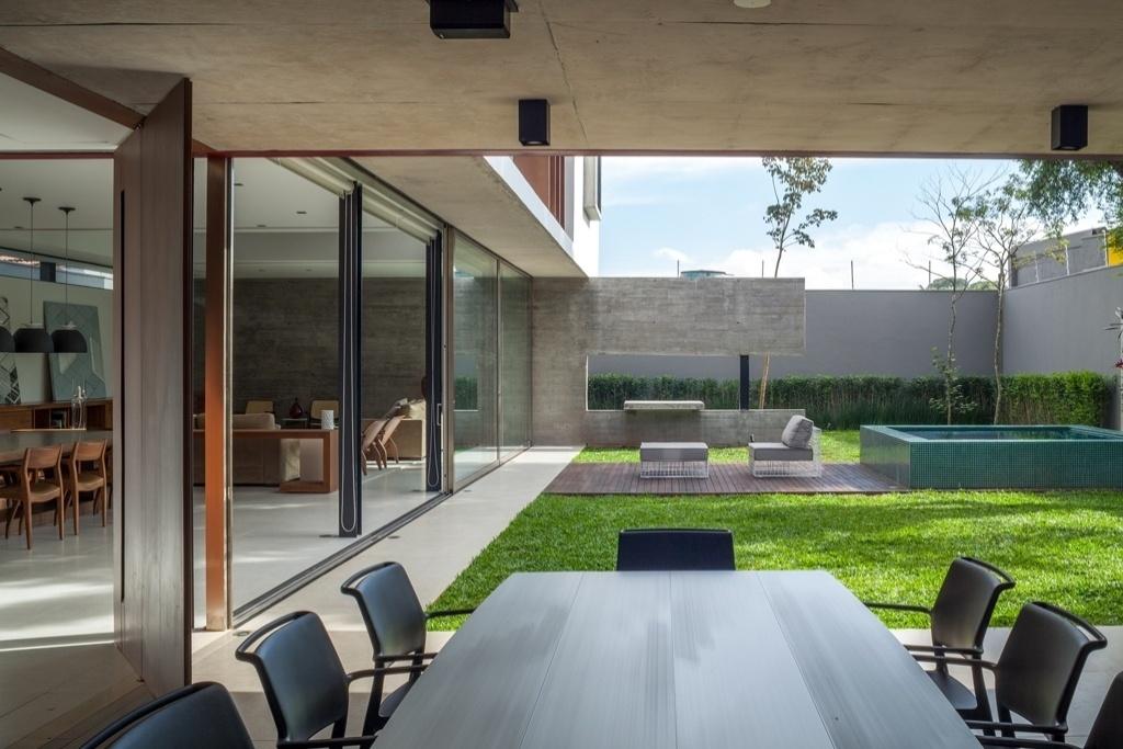 Da área coberta da churrasqueira, é possível visualizar o jardim com o ofurô e a parede estrutural em concreto no fundos da Casa Planalto