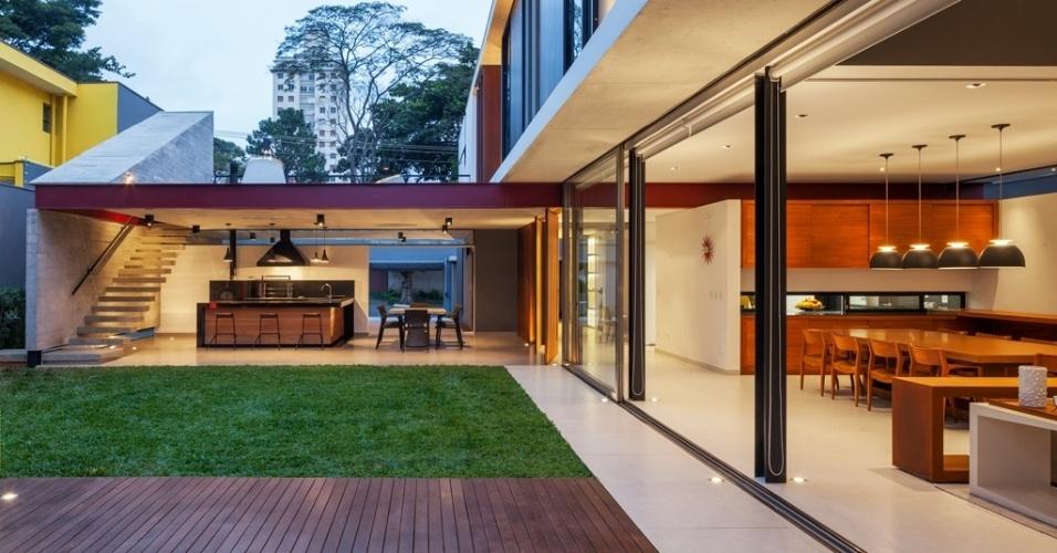 Do jardim, é possível visualizar a área da churrasqueira e as salas de jantar e estar. No espaço da churrasqueira, a escada de concreto, cujos degraus são fixados a uma parede lateral, estrutural, também em concreto, faz circulação entre os pavimentos