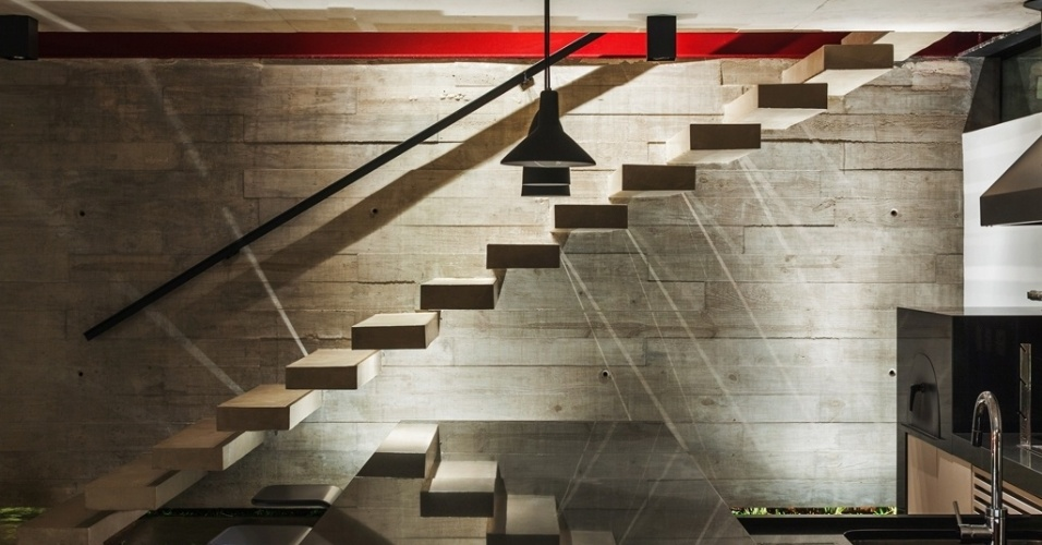 Na área de churrasqueira há uma parede de concreto, moldada em loco, em formas de pinus e ripas de espessuras e larguras variadas que produziram textura