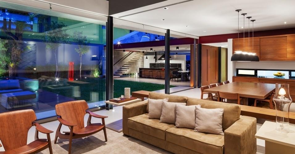 O jardim, a churrasqueira e a área social interna ? salas de TV, estar e jantar - estão completamente integrados por portas de vidro de correr ou por portas pivotantes de aço corten, em um grande espaço térreo livre de pilares