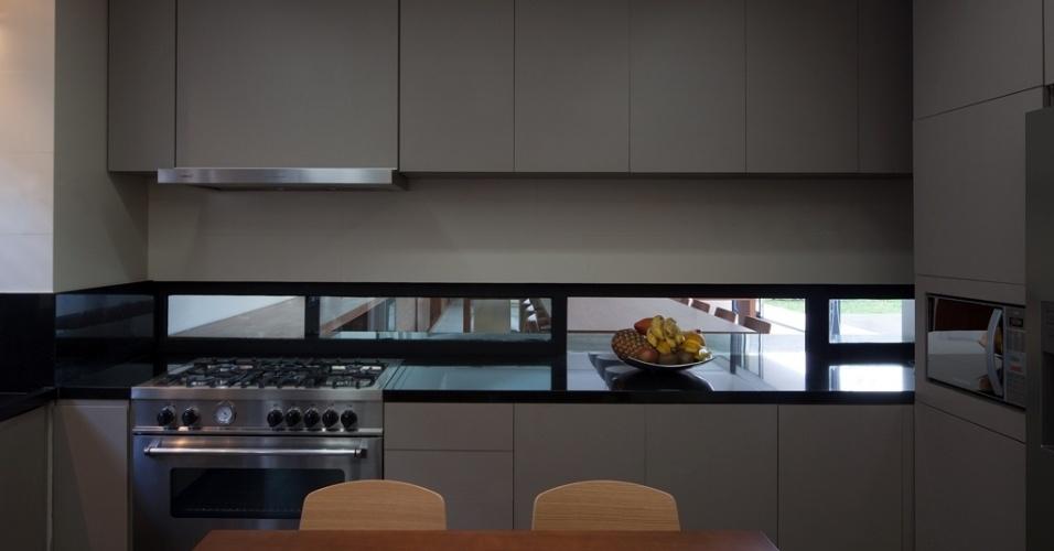 Um passa pratos em perfis metálicos, que comunica a cozinha à sala de jantar está, pelos dois lados, abaixo dos conjuntos de armários (Antico Ofício). O projeto da Casa Planalto é assinado pelo arquiteto Flavio Castro