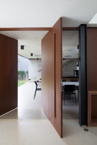 Uma porta pivotante em aço corten (Coppermax) comunica a área social interna da Casa Planalto com a churrasqueira. Os puxadores das portas também são desenhados pelo arquiteto Flavio Castro