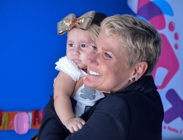 23.abr.2014 - Xuxa tira fotos com crianças na inauguração da Casa X