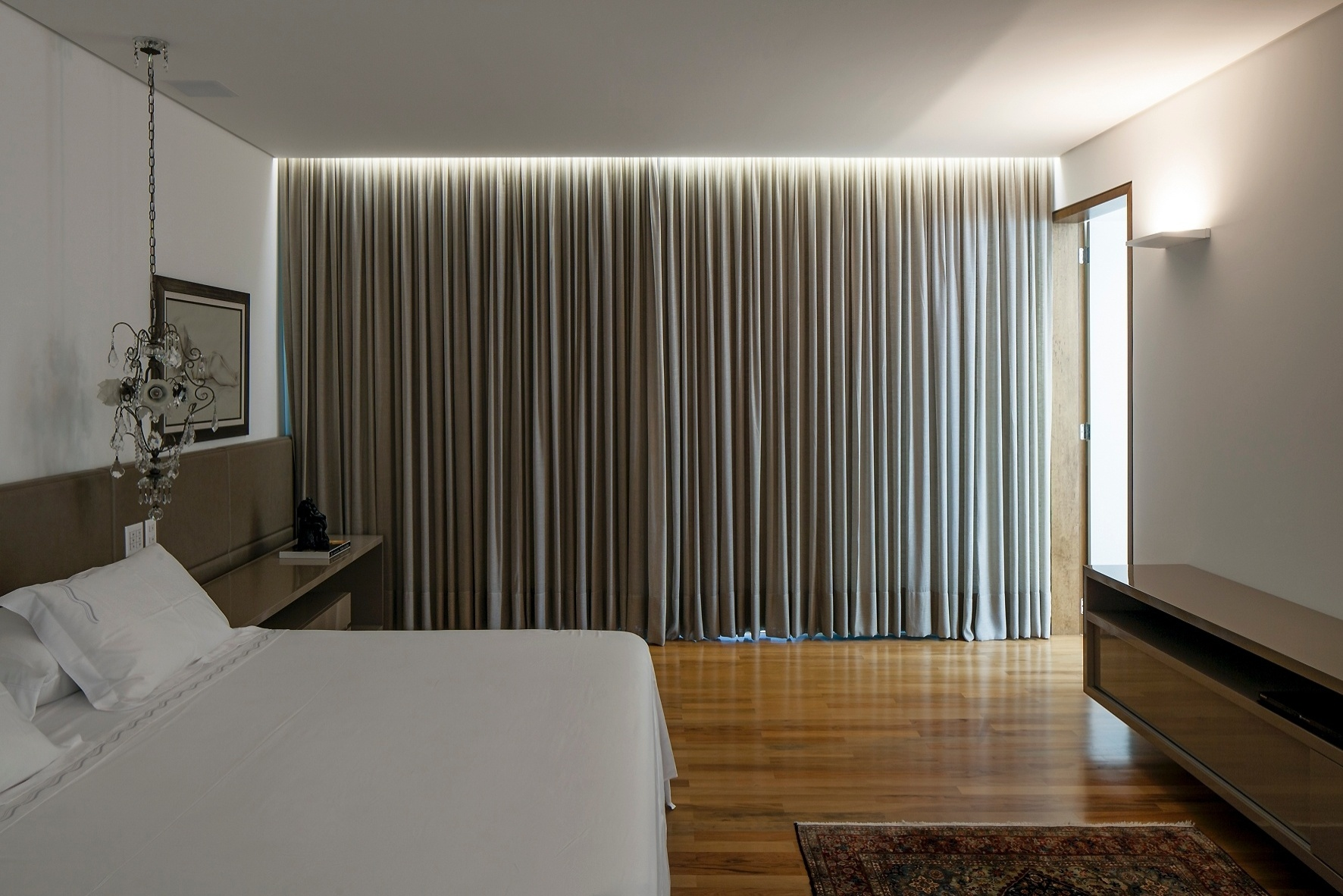 A atmosfera suave e intimista invade o dormitório do casal que tem cabeceira ocupando toda a extensão da parede, assim como a bancada em frente à cama