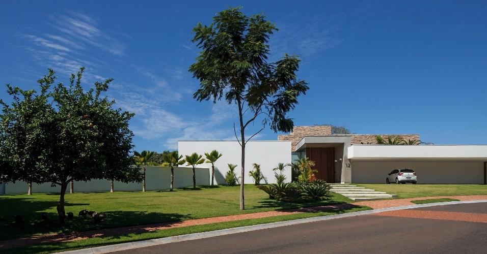 A fachada principal é marcada pela garagem com vão livre de 15 m, capaz de abrigar cinco automóveis. Um pórtico em concreto aparente destaca o hall de entrada e se estende até o corpo principal da residência