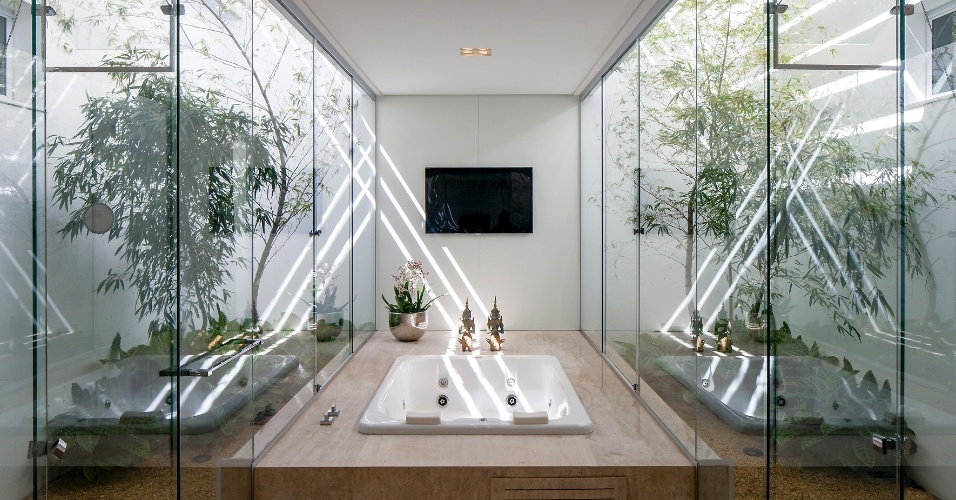 A suíte do casal possui uma ampla sala de banho, com hidromassagem ao centro e bucólicos jardins nas laterais, separados apenas por vidros. A TV na parede permite horas de relaxamento e entretenimento