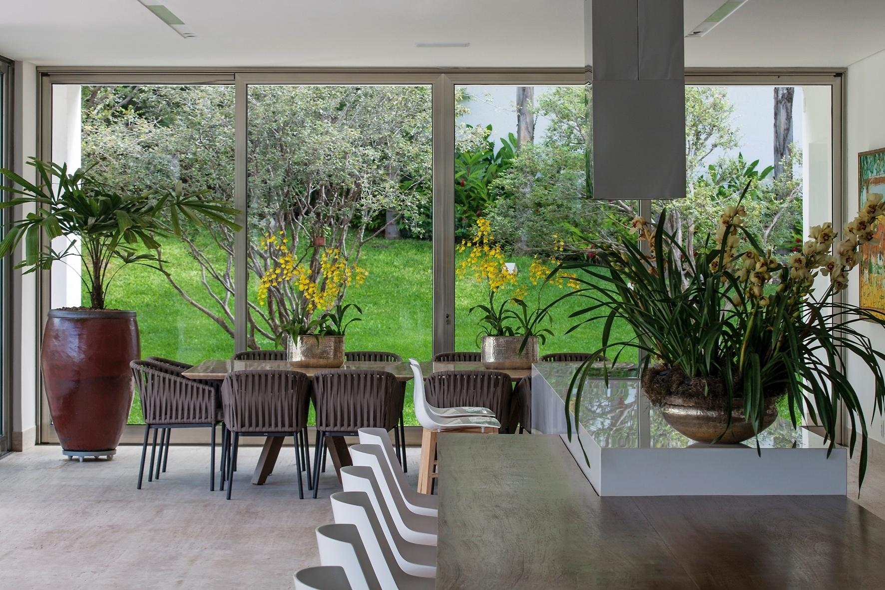 A varanda voltada para os jardins abriga um agradável espaço gourmet, onde estão dispostas a bancada com mesa acoplada, além de outra mesa para refeições