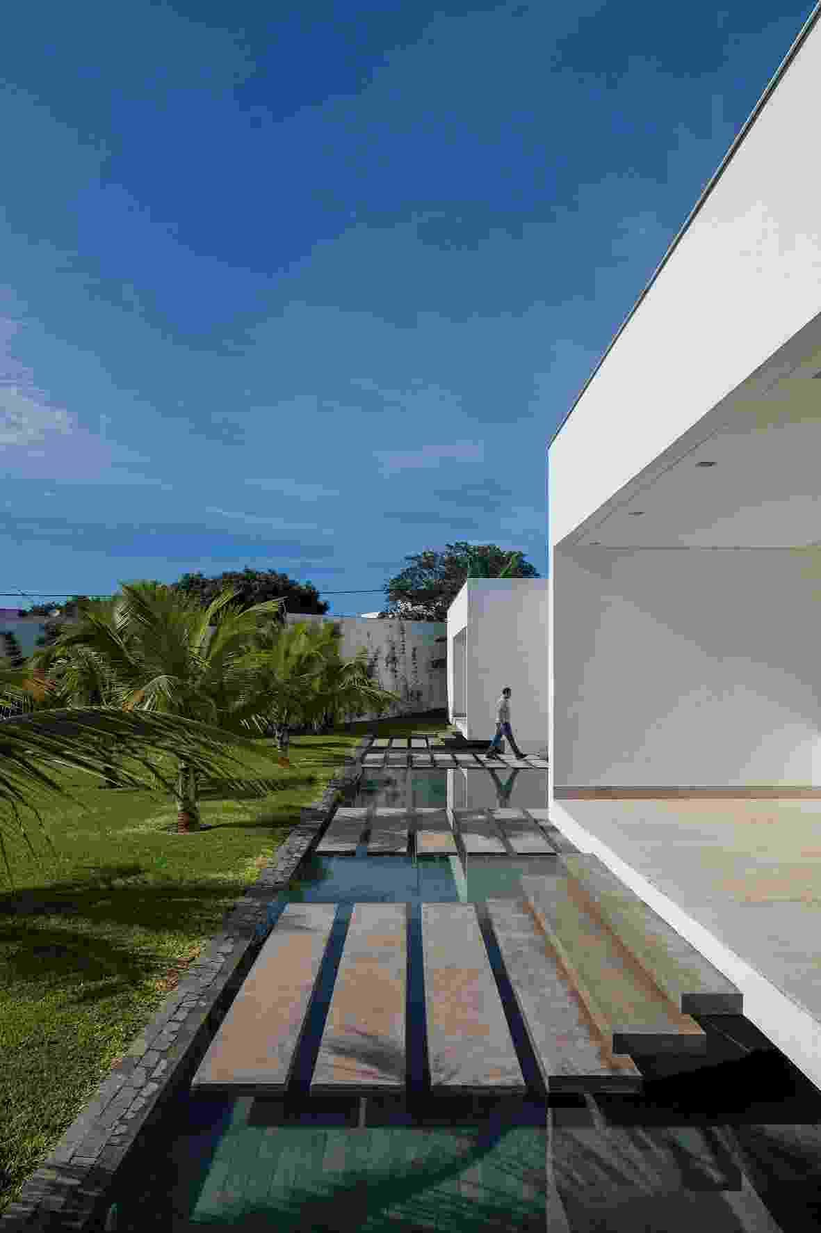 Aproveitando o suave desnível do terreno, criou-se um jardim e um espelho d?água que reflete o volume dos dormitórios, este elevado a 80 cm. O acesso aos quartos se dá por degraus apoiados em pilares centrais que dão a sensação visual de estarem flutuando - Leonardo Finotti/UOL