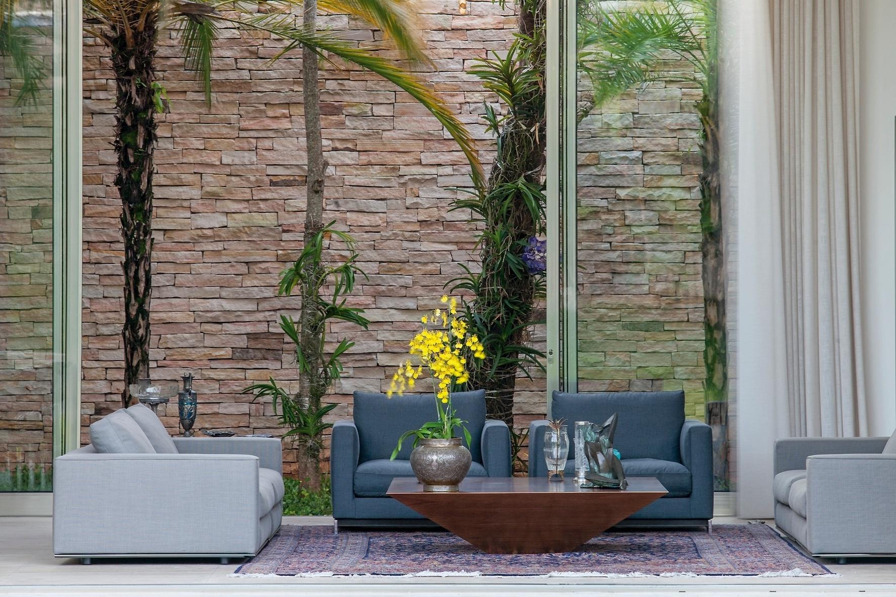 Com cinco metros de pé-direito, o living se abre para um jardim de inverno, onde uma árvore sibipiruna antiga foi preservada. O revestimento em pedra concede um visual rústico em harmonia com a discreta elegância da decoração