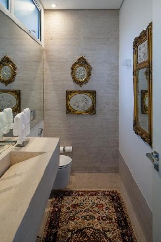 O mármore travertino reveste o piso e também uma das paredes do lavabo, além da cuba e da bancada, dando um ar sofisticado ao ambiente. As janelas altas deixam entrar luz natural e ventilação