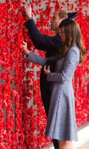 25.abr.2014 - Em Canberra, na Austrália, Kate Middleton e o Príncipe William colocam flores em painel que homenageia os soldados australianos que lutaram na Primeira Guerra Mundial