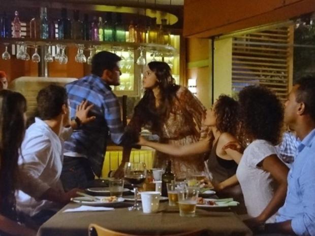 Luiza e André discutem na frente dos amigos em um bar