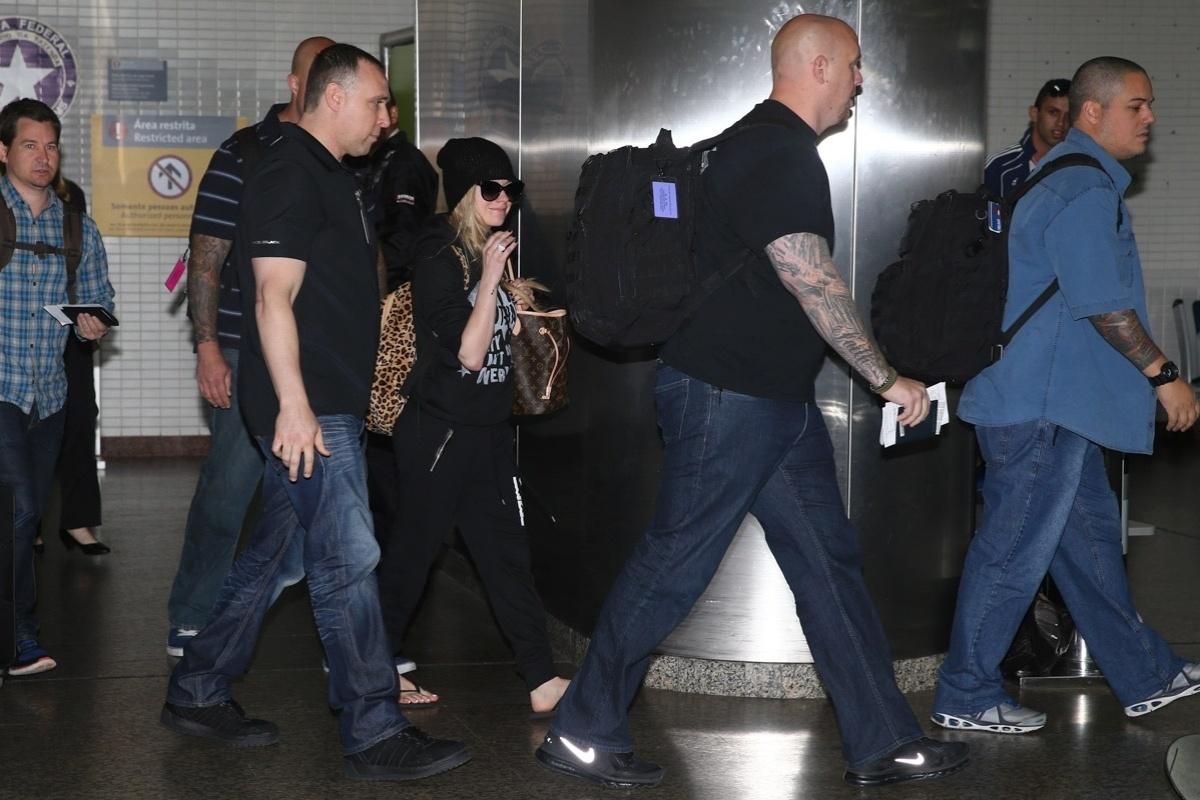 28.abr.2014- Avril Lavigne desembarca em São Paulo de chinelos, gorro e óculos escuros