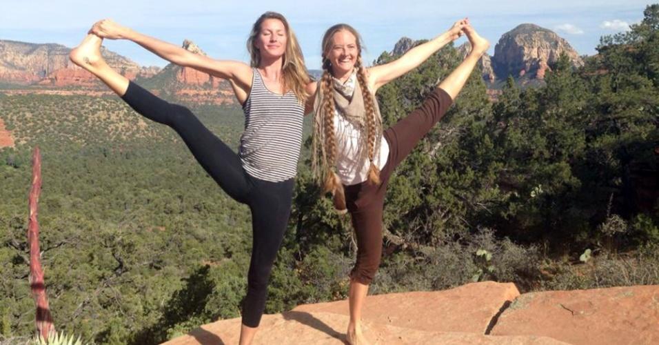 26.abr.2014 - Ao lado de amiga, Gisele Bündchen faz pose de ioga e estica as pernas durante retiro espiritual no estado norte-americano do Arizona