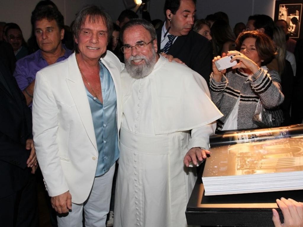 29.abr.2014 - Roberto Carlos recebe o carinho do Padre Antônio Maria durante o lançamento de biografia fotográfica oficial em shopping de São Paulo