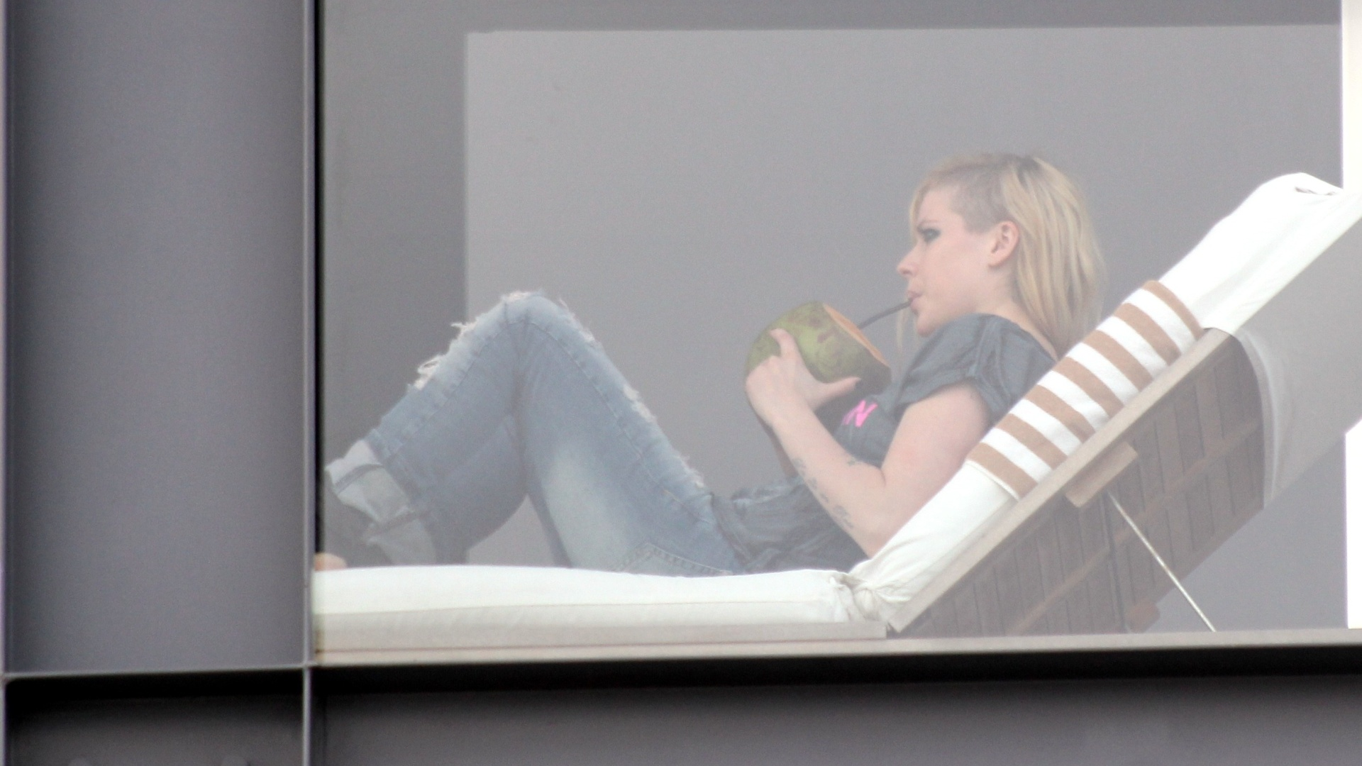2.mai.2014 - Avril Lavigne apareceu bebendo água de coco na sacada do hotel onde está hospedada, no Arpoador, zona sul do Rio de Janeiro