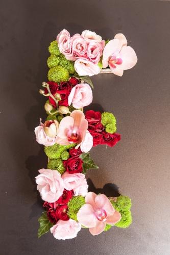 A designer explica que pensou o arranjo adotando cores complementares: tons de rosa e vermelho que se destacam sobre os verdes. Para criar textura, Whitaker enfincou os caules em alturas diferentes