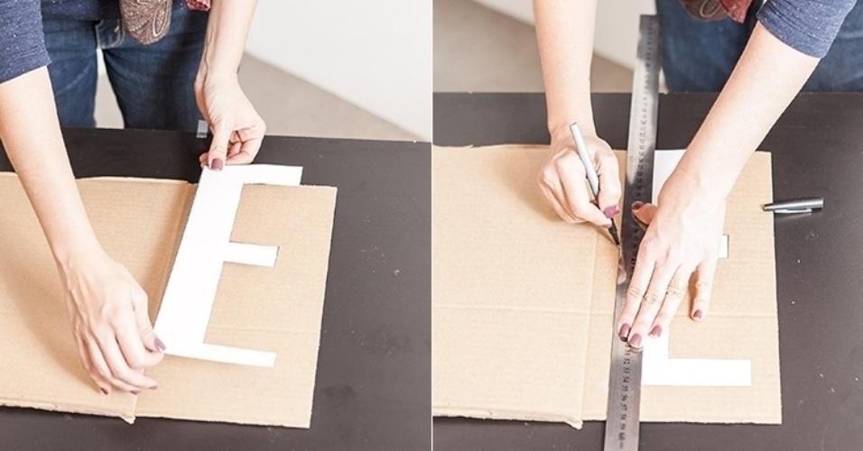 Após recortar as letras, com a fita adesiva, cole o caractere sobre um pedaço de papelão. Em seguida, marque com a caneta o contorno da letra sobre o papelão usando a régua como apoio. Repita essa etapa com cada caractere