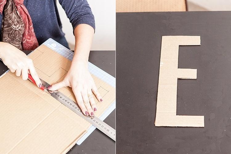 Depois de contornar as letras no papelão, sobre a base de corte, recorte cada uma delas com o estilete, acompanhando o traçado feito anteriormente. Essas letras em papelão serão o fundo das caixas para o arranjo floral. Reserve-as