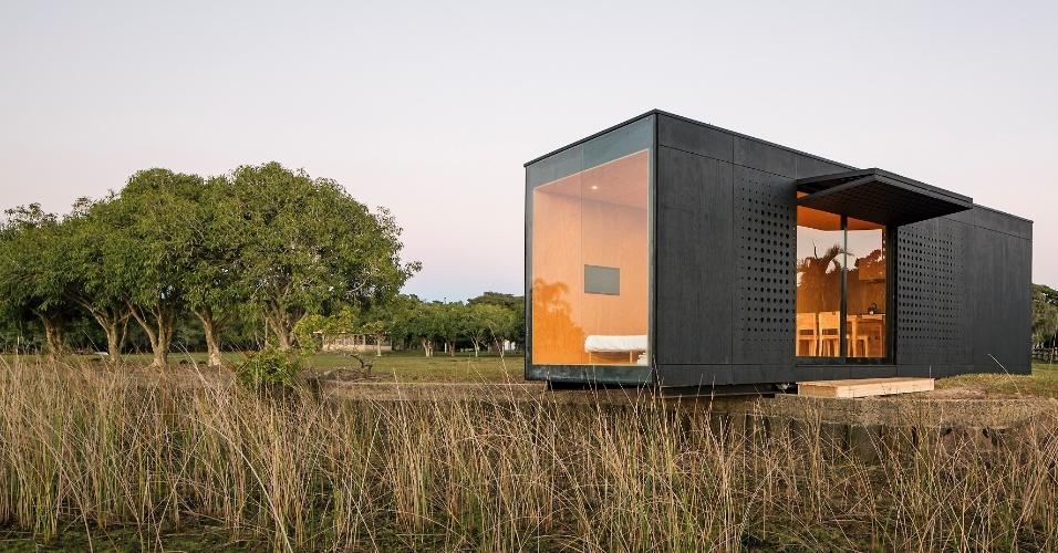 A fachada do MiniMod, projetado pelo escritório MAPA, é marcada pela porta de correr em vidro e um portão basculante que funciona como marquise na entrada da casa. Perfurações em círculo têm efeito estético original