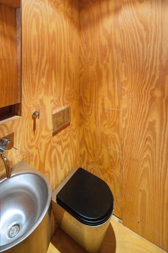 Com área compacta, o banheiro é prático, dotado das instalações necessárias para o bom funcionamento e possui o mesmo revestimento em madeira do restante do módulo