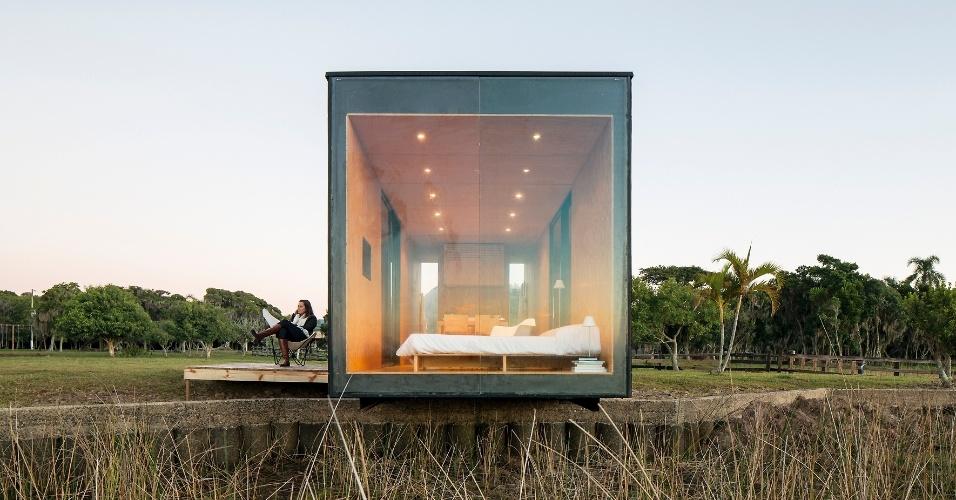 Com fechamento em vidro nas extremidades, a casa MiniMod, criada pelo escritório MAPA, está integrada com a natureza e ainda possui um pequeno deck de madeira na entrada, servindo de varanda