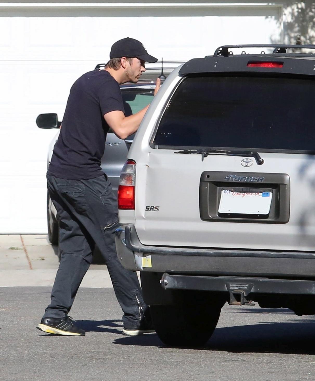 12.mai.2014 - Ashton Kutcher tira satisfações com fotógrafo que estava posicionado perto de sua casa em Los Angeles, na Califórnia