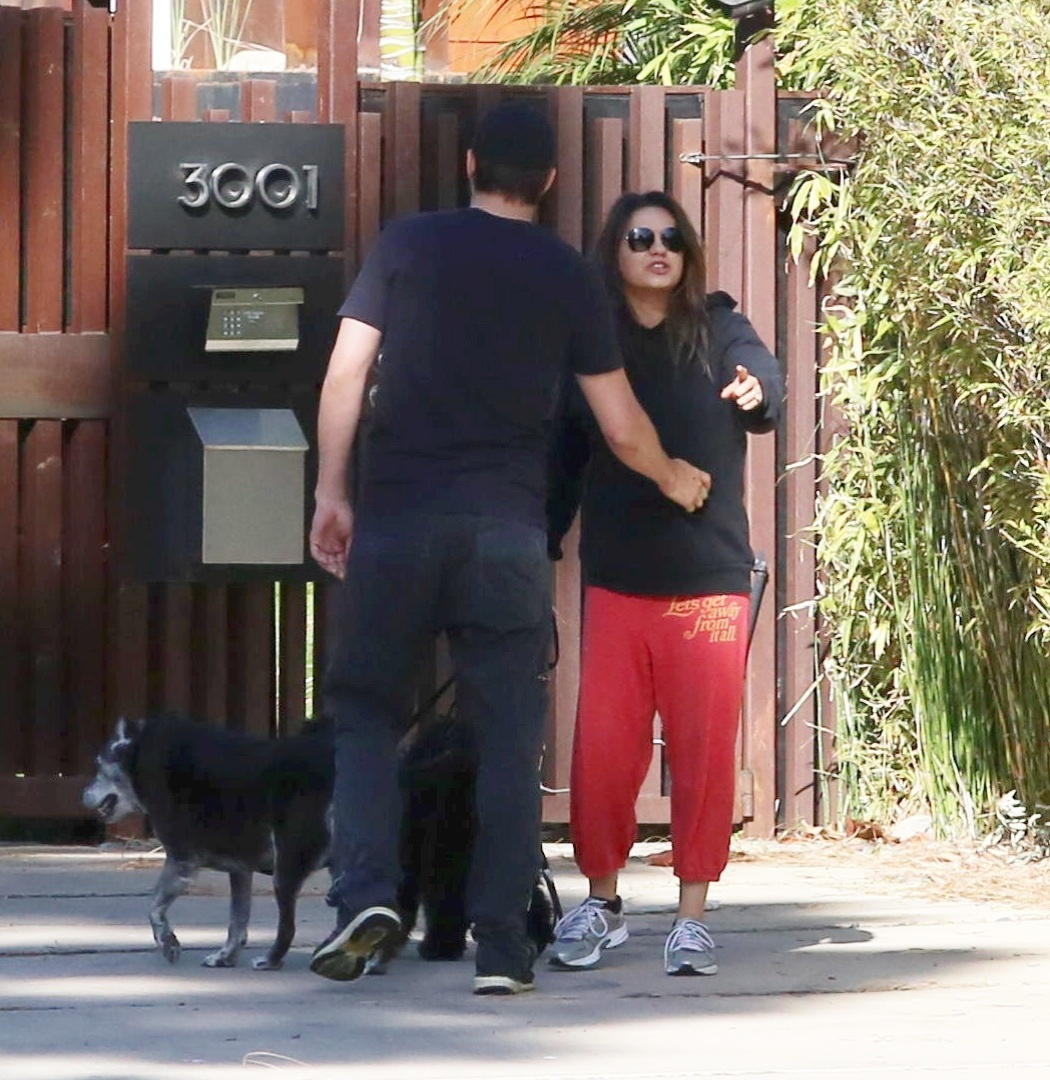 12.mai.2014 - Mila Kunis se irrita com fotógrafo e Ashton Kutcher tenta fazê-la voltar para dentro da casa do casal em Los Angeles, na Califórnia