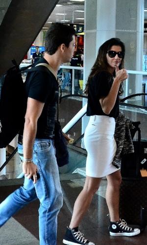 13.mai.2014- Deborah Secco embarca em aeroporto Santo Dumont, no Rio, com o namorado, Bruno Torres. Estilosa, a atriz usou uma saia branca, com tênis e camisa preta