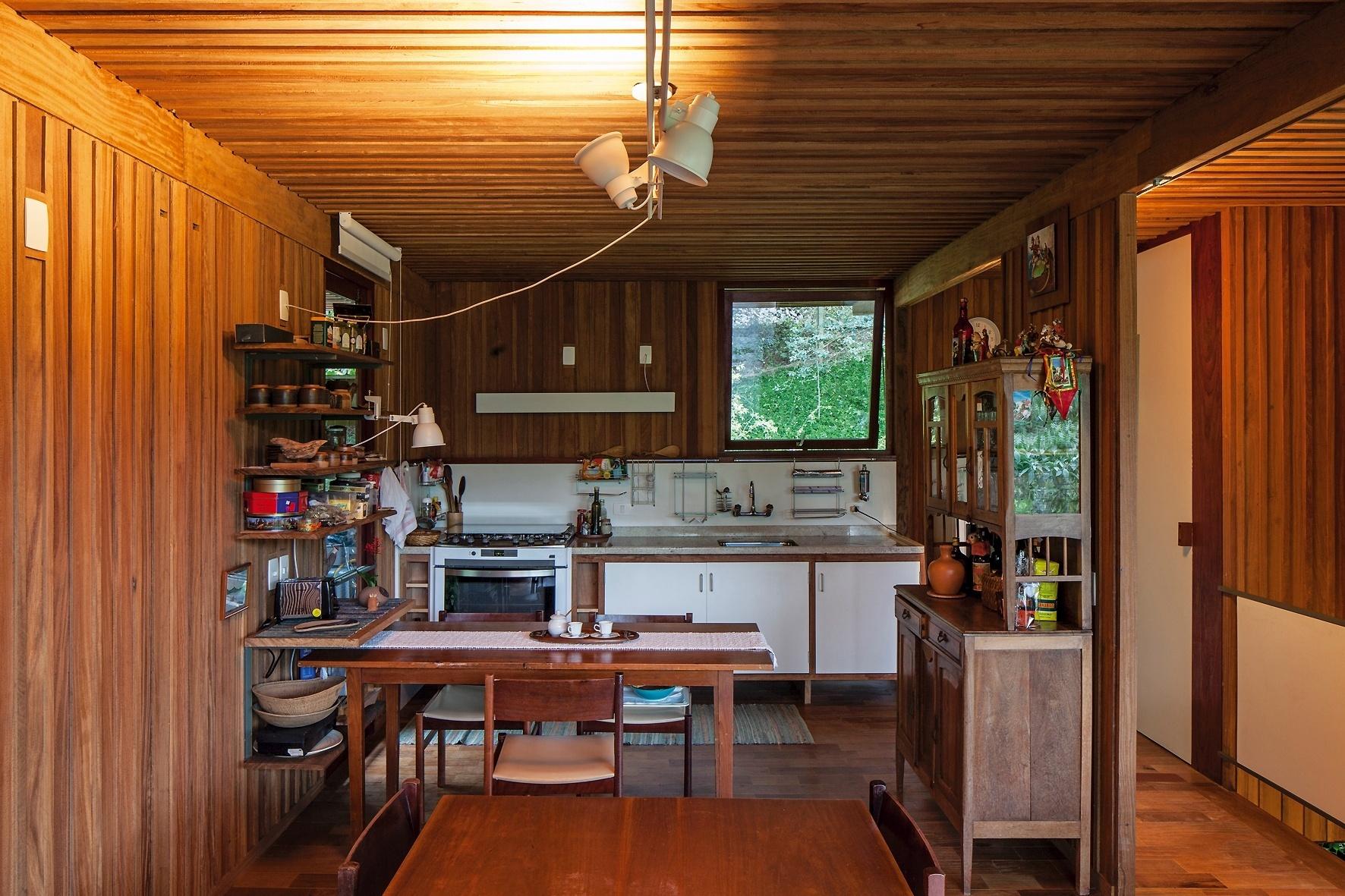 Totalmente aberta para o living, a cozinha da Casa Vila Taguaí é prática, com prateleiras para utensílios e mesa para pequenas refeições. O projeto tem a assinatura da arquiteta Cristina Xavier e do engenheiro Hélio Olga