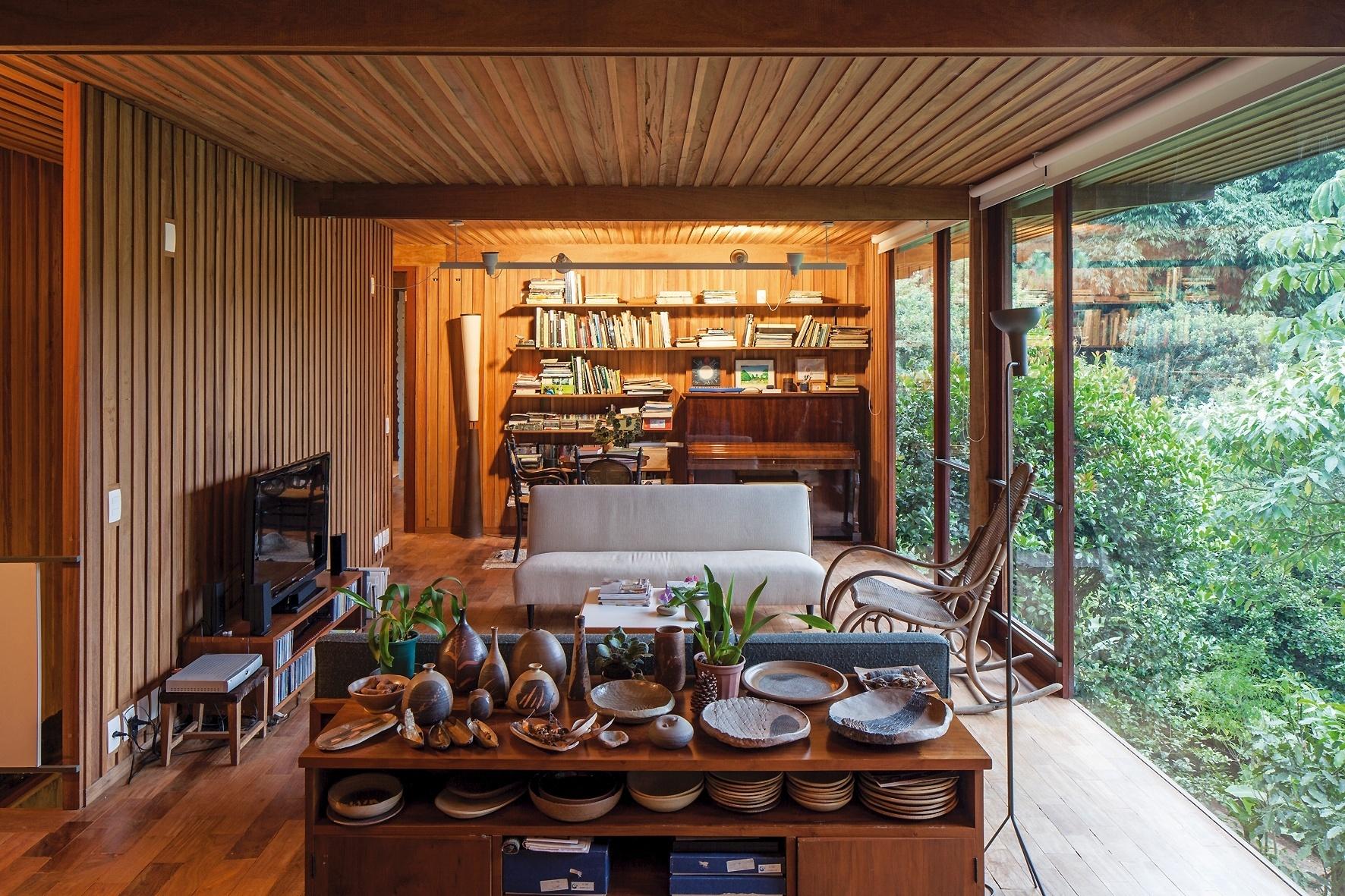 A madeira cumaru, que forma toda a estrutura da casa, também compõe a decoração do living. O material está em bancadas, bufês, estantes e aparadores. Localizada em Carapicuíba (SP), a Casa Vila Taguaí foi projetada pelos profissionais Cristina Xavier e Hélio Olga
