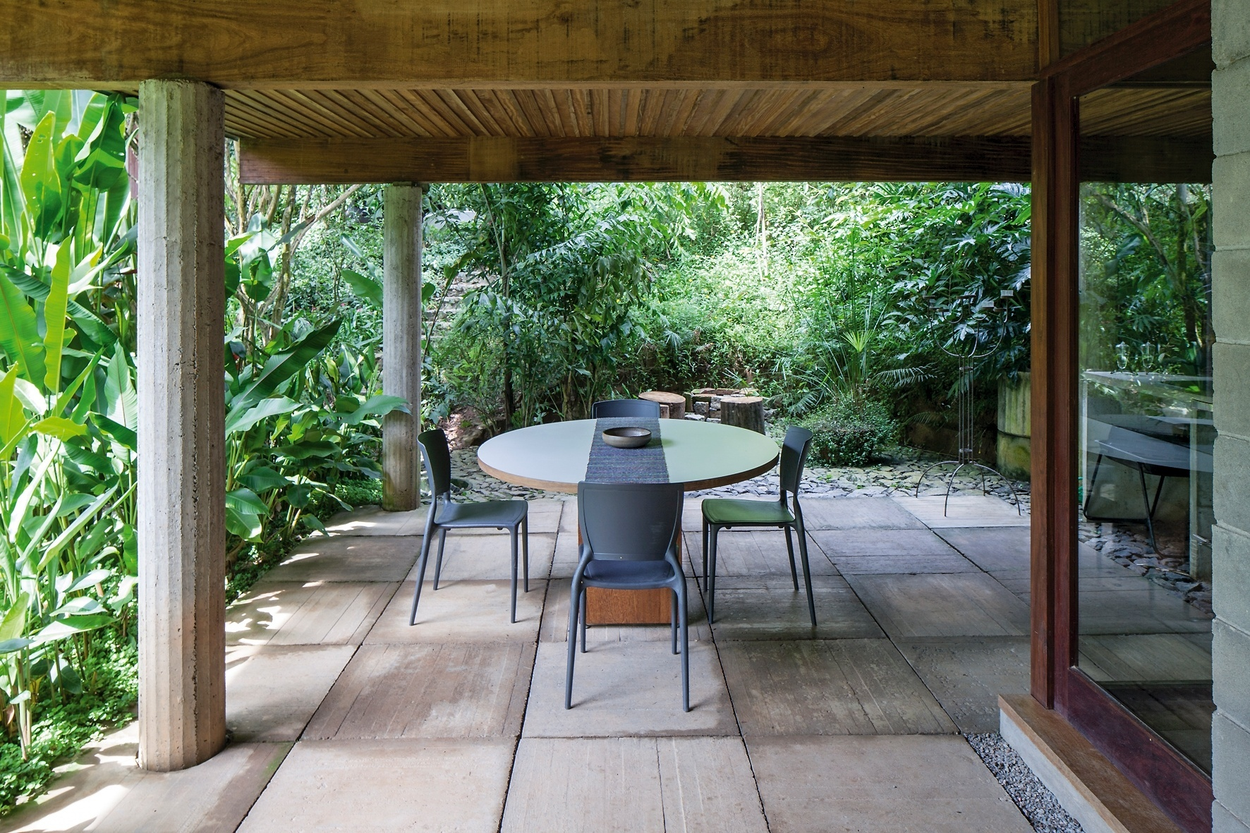 Deste ângulo, é possível observar a integração total do terraço com a natureza. A madeira aquece visualmente o espaço e quebra a rigidez do concreto usado no piso e nas colunas. O projeto da Casa Vila Taguaí, localizada em Carapicuíba (SP), é uma parceria da arquiteta Cristina Xavier e do engenheiro Hélio Olga