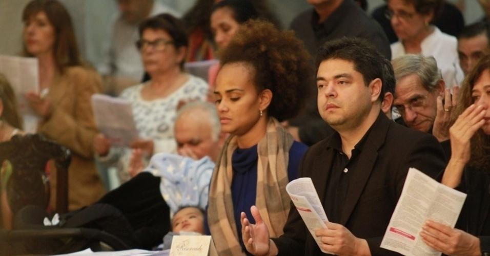 14.mai.2014 - A cantora Luciana Mello com o filho Tony nos braços reza durante missa de sétimo dia do seu pai, o cantor Jair Rodrigues, em São Paulo