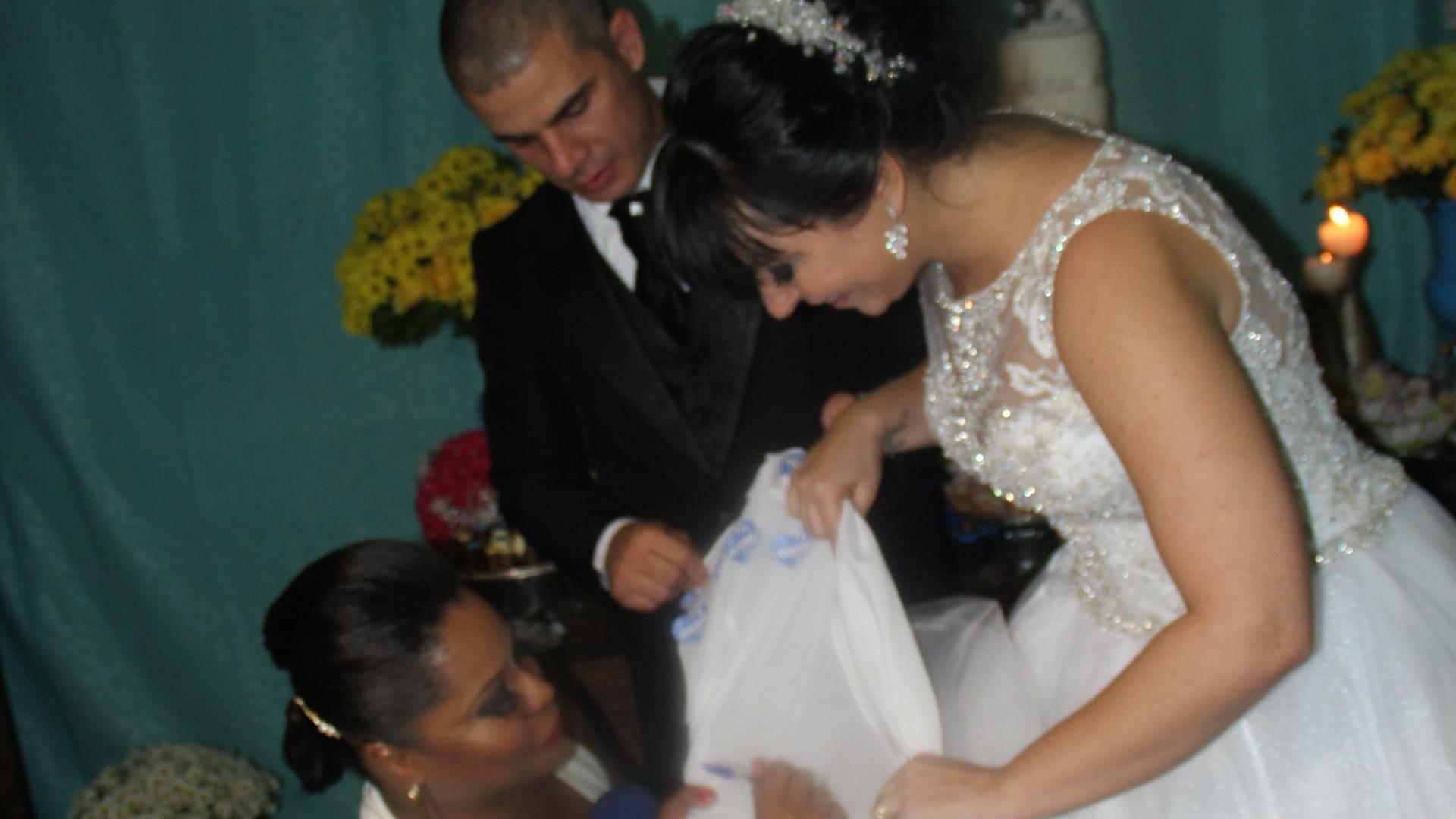 16.mai.2014 - Adriana Bombom escreveu seu nome na barra do vestido da noiva, Luciana Picorelli
