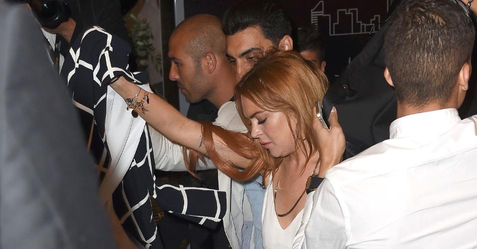 21.mai.2014 - Lindsay Lohan foi cercada pela imprensa ao chegar ao hotel onde está hospedada, em Cannes. Acompanhada por um rapaz, ela teve dificuldade para conseguir escapar do tumulto