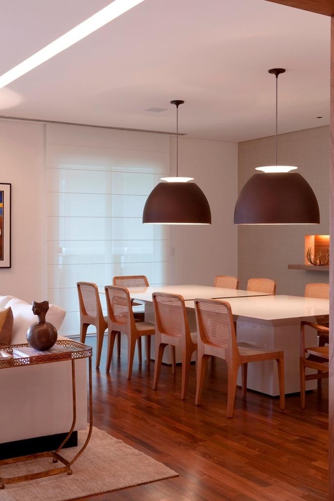 Para destacar a sala de jantar do living integrado com superfícies predominantemente brancas, o projeto de arquitetura do escritório Messa Penna, adotou o cinza para colorir a parede (à dir.). O amadeirado e o marrom dos elementos de decoração sobressaem em relação ao fundo neutro e aquecem o ambiente