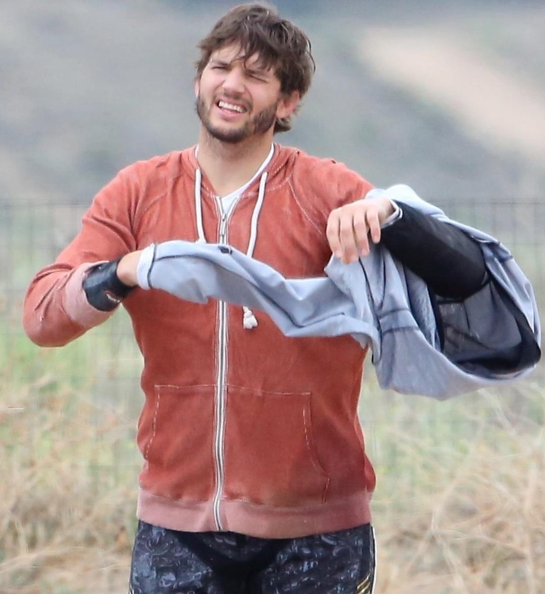 22.mai.2014 - Ashton Kutcher tira jaqueta de motocross após praticar o esporte em um parque próximo de Los Angeles, na Califórnia