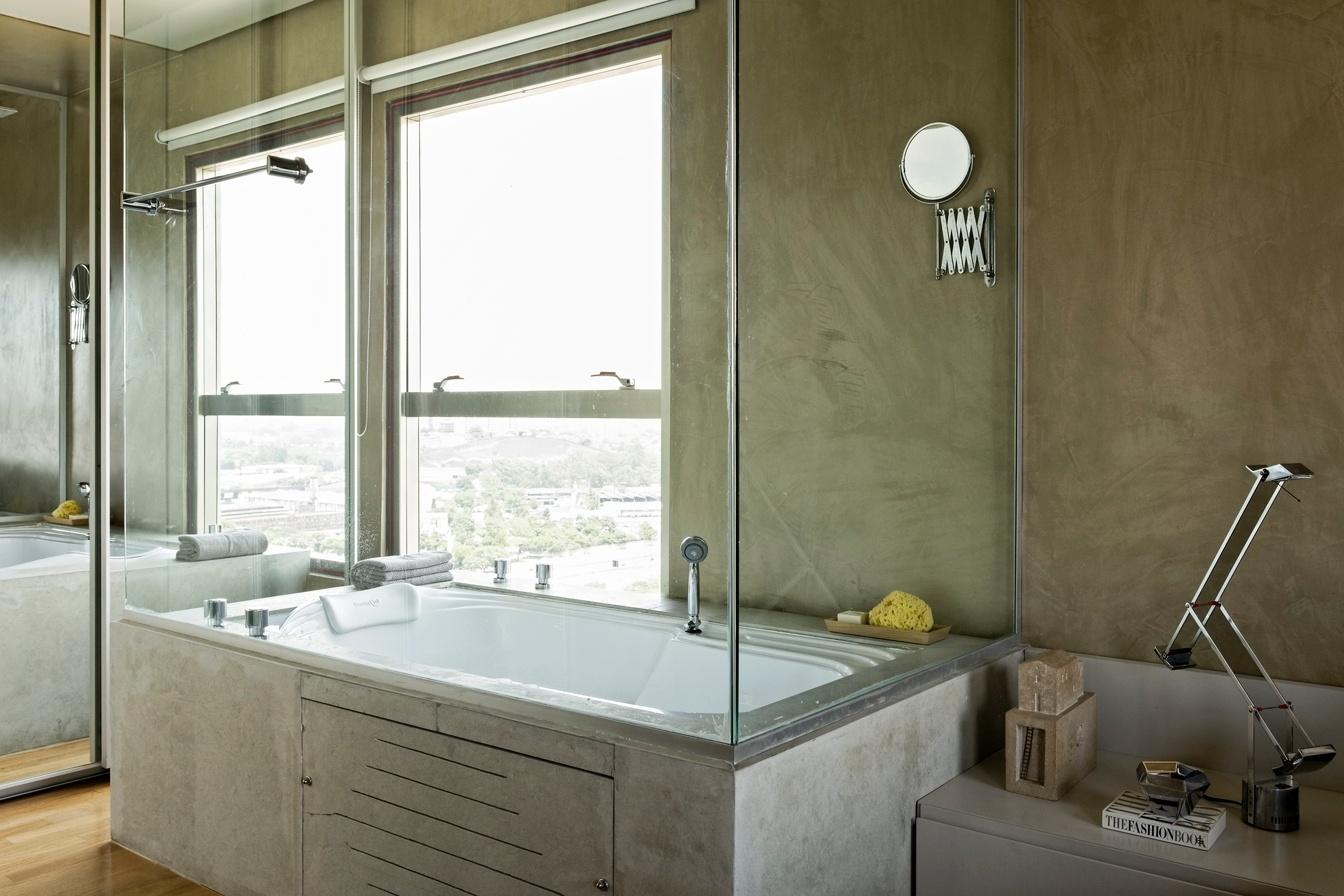 A banheira revestida em limestone recebeu fechamento em vidro na parte superior e foi estrategicamente colocada junto à janela, de modo que o proprietário pudesse apreciar a paisagem da cidade durante o banho. O projeto de reforma do Loft Vila Leopoldina leva a assinatura do arquiteto Diego Revollo